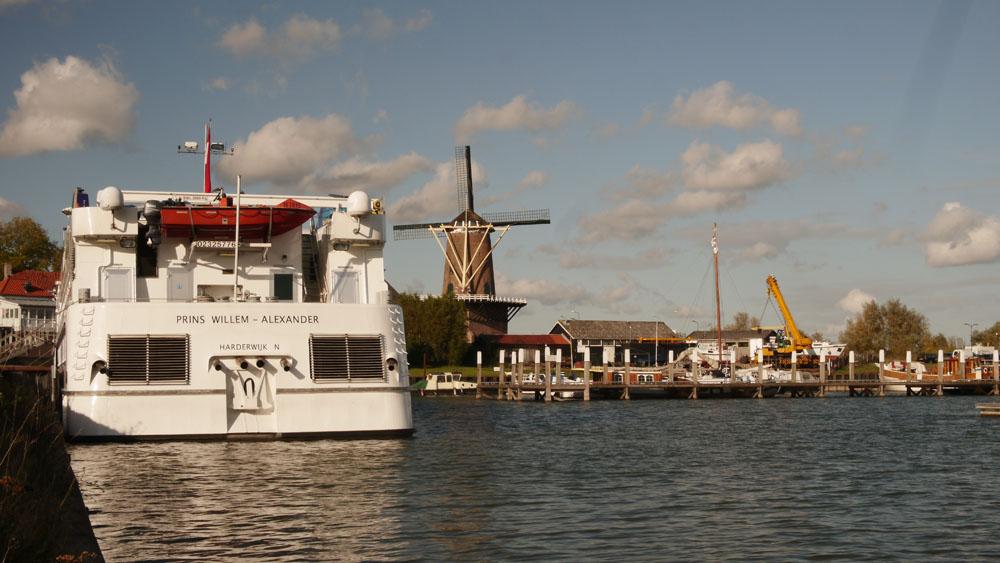"""De haven van Wijk bij Duurstede met de walpoortmolen """"de Rijn en Lek"""" in het verschiet. Prominent in beeld is een riviercruiseschip waarvan de naam onlangs toch echt is achterhaald."""