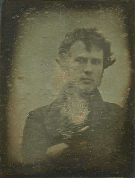 Het eerste fotografische portret dat ooit van een persoon is gemaakt, is het zelfportret op daguerrotype vanRobert Cornelius uit 1839. Origineel in Library of Congress. Beeld is in publiek domein.