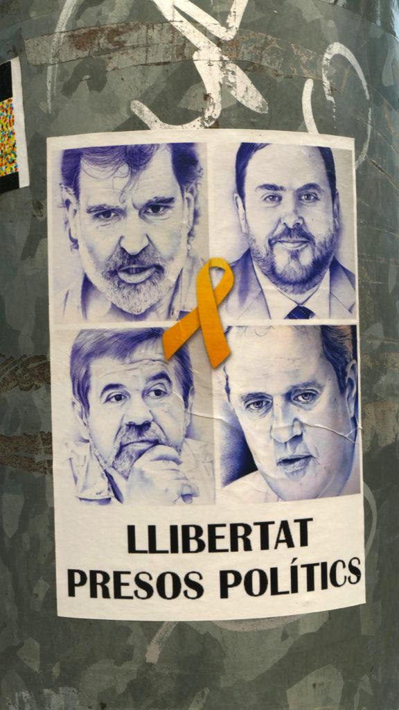 """""""Vrijheid voor de politieke gevangenen"""", poster met vier portretten en een gele strik (symbool van de oproep tot veilige terugkeer van de vervolgden). Jordi Cuixart (linksboven), Oriol Junqueras (rechtsboven), Jordi Sànchez (linksonder), Joaquim Forn. Foto ©2018 Huib J. Lirb"""