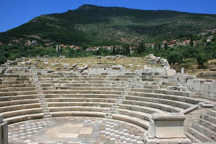 Het theater van de stad Messene (die na bevrijding van de heloten door Epaminondas in 369 v. Chr. is gesticht over de ruïnes van de oorspronkelijke nederzetting) met de berg Ithomi en het moderne dorp Mavrommati in het verschiet (Foto 2010 Stefan Artinger, (Wikimedia Commons Public Domain)